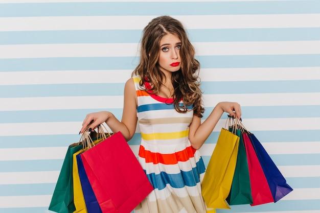 Chica glamorosa triste posando después de ir de compras. señora molesta con maquillaje de moda con bolsas de tienda.