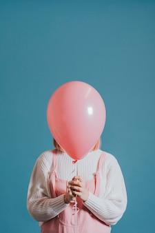 Chica con un globo de helio rosa.