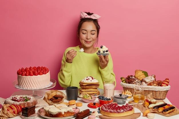 Chica golosa hambrienta sostiene cupcake en una mano, cuchara con crema en la otra, obtiene porción de azúcar disfruta de un delicioso refrigerio durante el evento festivo mantiene los ojos cerrados por placer.