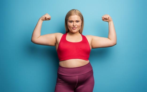 Chica gorda hace gimnasio en casa. expresión satisfecha fondo cian