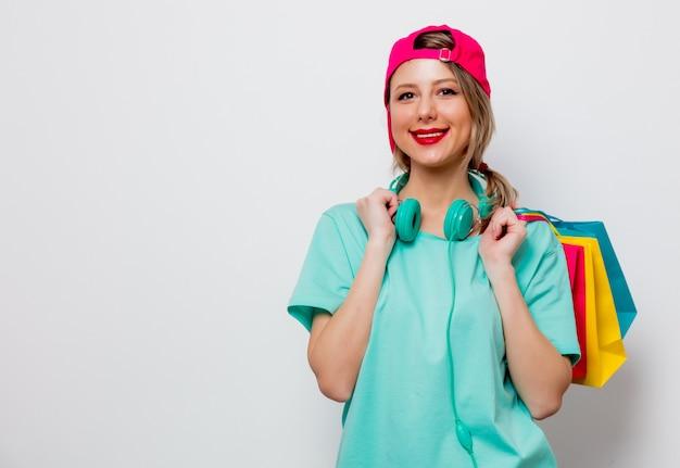 Chica con gorra rosa y camiseta azul con bolsas de la compra.