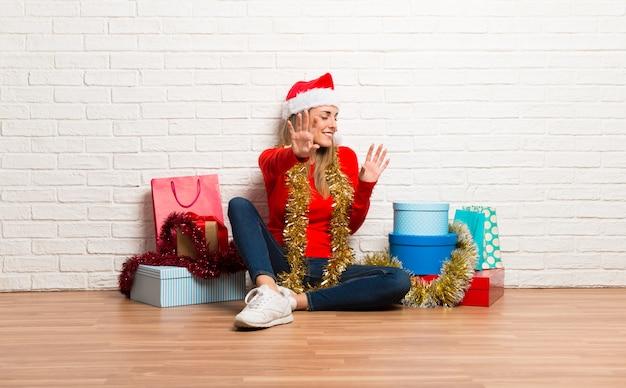 Chica con gorro navideño y muchos regalos celebrando las fiestas navideñas es un poquito.