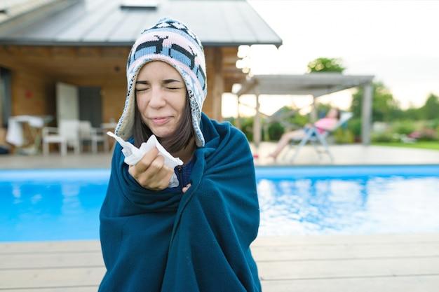 Chica en un gorro de punto con cuadros con pañuelo estornuda