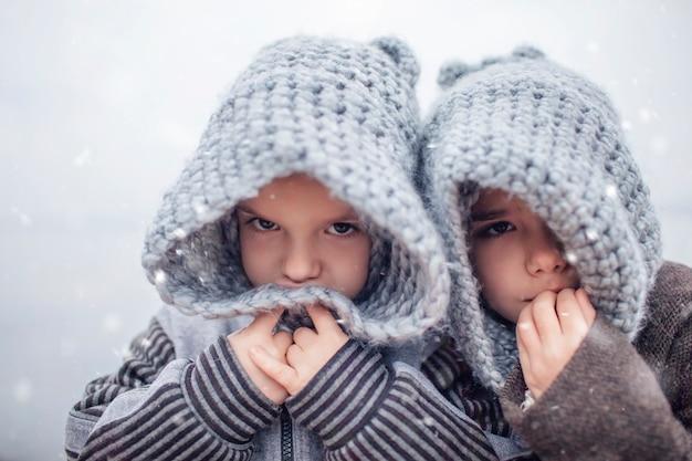 Chica con gorro de punto gris abrazando a su hermano pequeño congelado