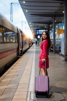 Chica con gran bolsa de carro en la estación de tren