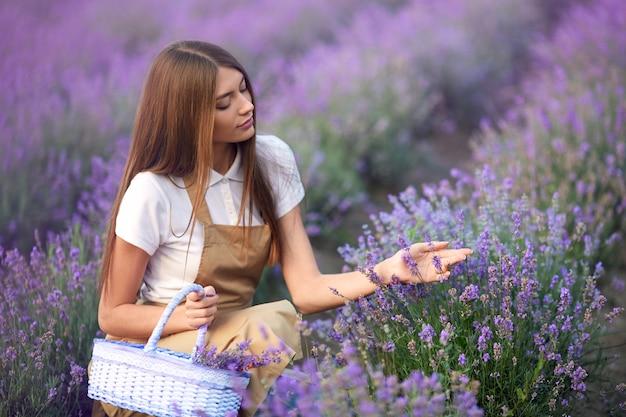 Chica de granja feliz con cesta de flores en campo lavanda
