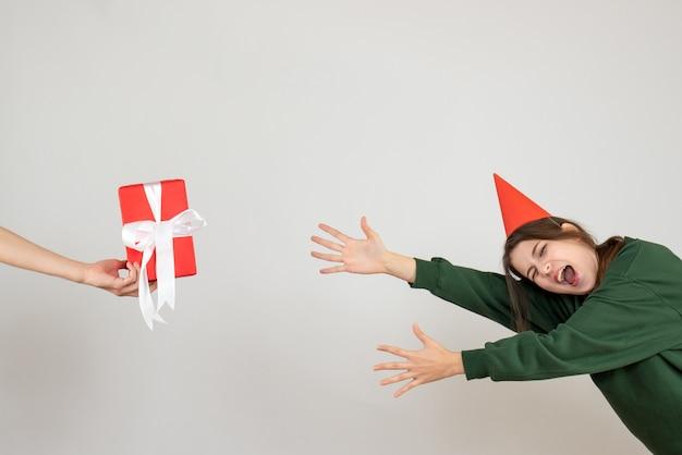 Chica gritando con gorro de fiesta tratando de atrapar el regalo en la mano humana sobre blanco
