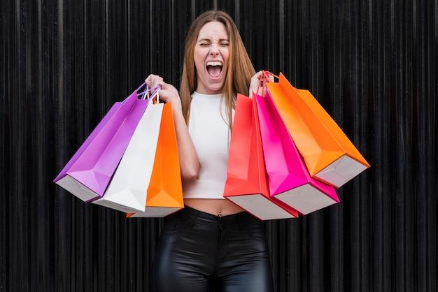 Chica gritando mientras sostiene bolsas de compras