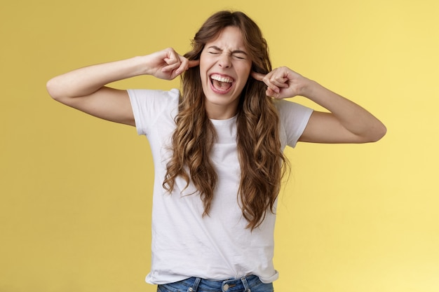 Chica gritando molesta demanda dejar de tocar la guitarra. mujer irritada molesta cerrar los ojos gritando tapón decepcionado dedos índices agujeros para los oídos disgustado fuerte ruido terrible atril fondo amarillo