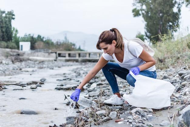 Chica con guantes azules agachada en la orilla del río sacando plástico del agua para reciclar
