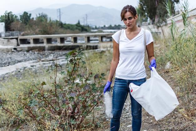 Chica con guantes azules de pie en la orilla del río mirando a la cámara con una botella de plástico en la mano para reciclarla