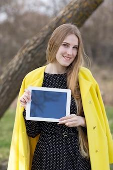Chica guapa en abrigo con tableta