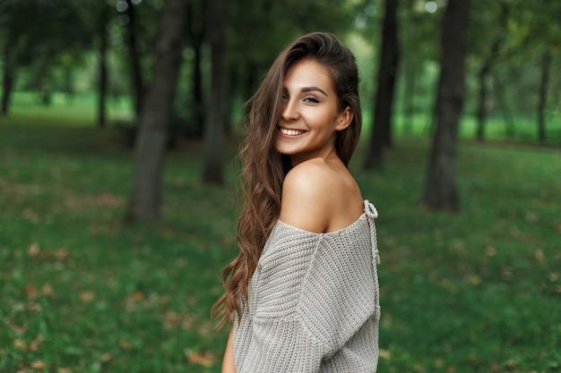 Chica guapa alegre con una hermosa sonrisa en un suéter gris cerca de los árboles en el parque