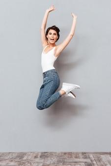 Chica guapa alegre saltando y mirando a la cámara sobre fondo gris