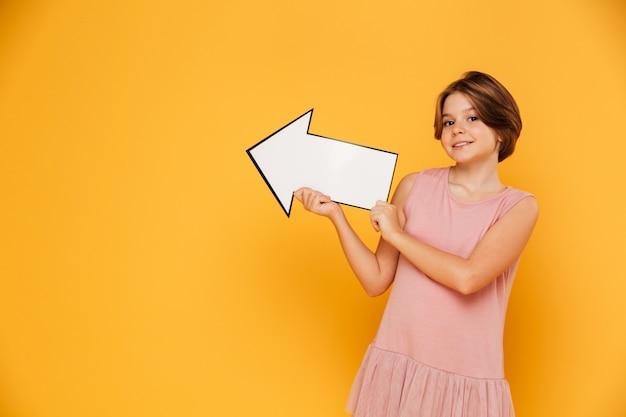 Chica guapa alegre sosteniendo flecha izquierda y mirando a cámara