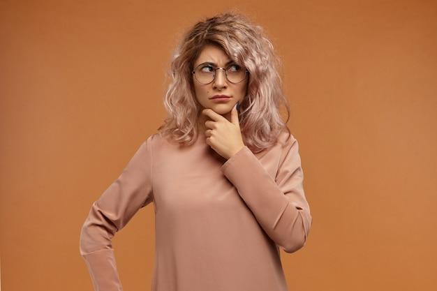 Chica guapa con anteojos redondos de moda frotando la barbilla y mirando hacia arriba, sin estar seguro de tener dudas acerca de tomar una decisión importante.