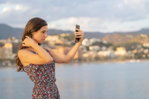 Chica guapa arregla su cabello con la cámara de su teléfono