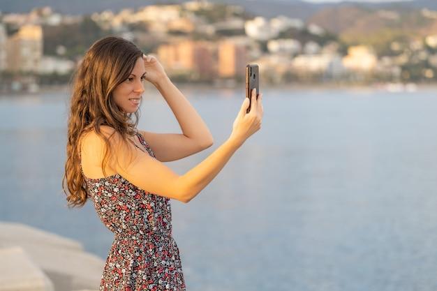 Chica guapa arregla su cabello largo con la cámara de su teléfono inteligente