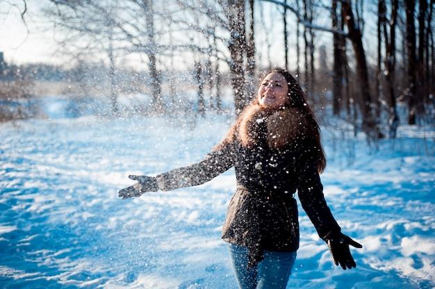Chica guapa arroja nieve en un parque de invierno