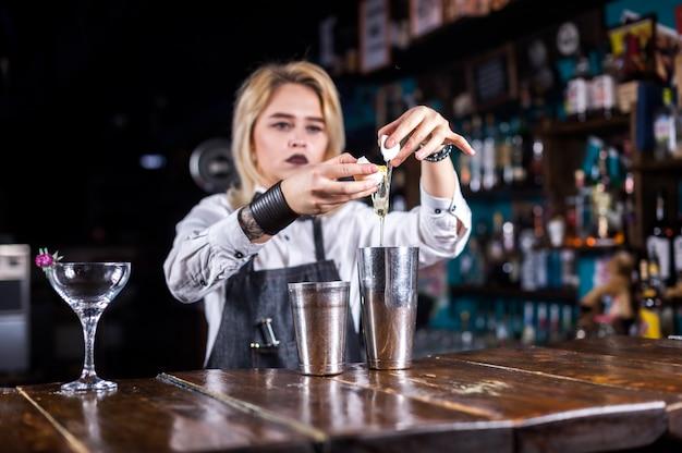 Chica guapa bartender hace un cóctel mientras está de pie cerca de la barra del bar en la discoteca