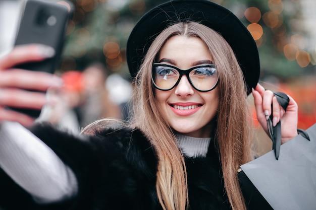Chica guapa con bolsas de compras en las manos hace una selfie en el fondo de las luces de un árbol de navidad.