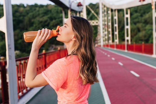 Chica guapa con cabello ondulado bebiendo agua después de maratón. señora caucásica refinada posando en la pista de ceniza durante el entrenamiento.