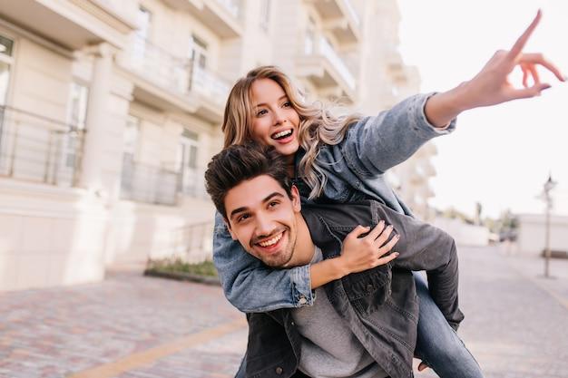 Chica guapa caucásica caminando por la ciudad con su novio. hombre morena sonriente pasar el fin de semana con su novia.