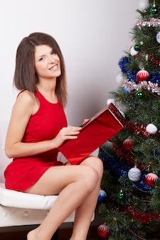 Chica guapa cerca del árbol de navidad