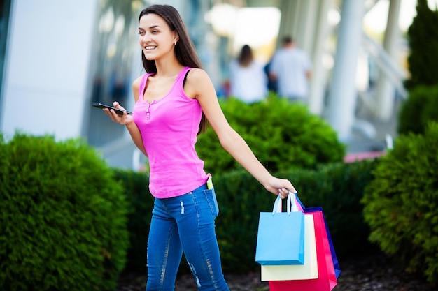 Chica guapa cerca del centro comercial tiene bolsas de colores