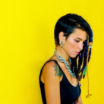 Chica guapa de colombia con rastas y piercings sobre pared amarilla colorida
