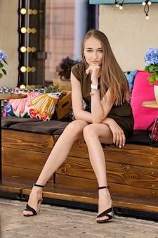 Chica guapa en un corto vestido color caqui sentada en una terraza de café