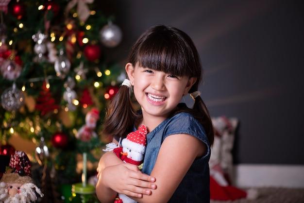 Chica guapa en decoración navideña abrazando a un muñeco de santa claus