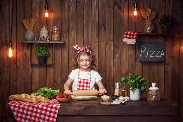 Chica guapa en delantal a cuadros desplegando masa para pizza