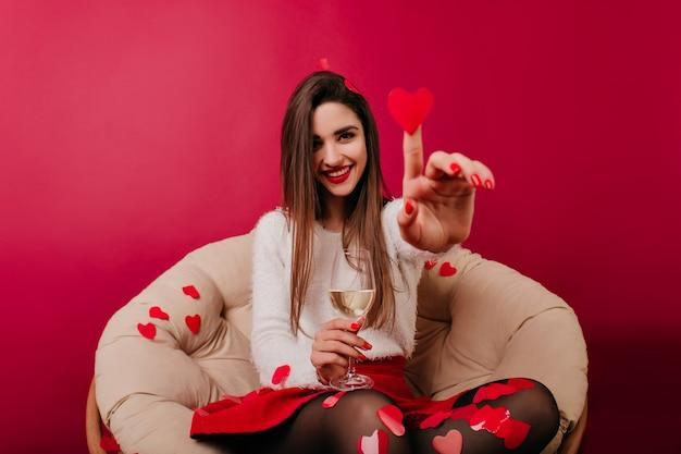 Chica guapa divirtiéndose en el día de san valentín y jugando con confeti