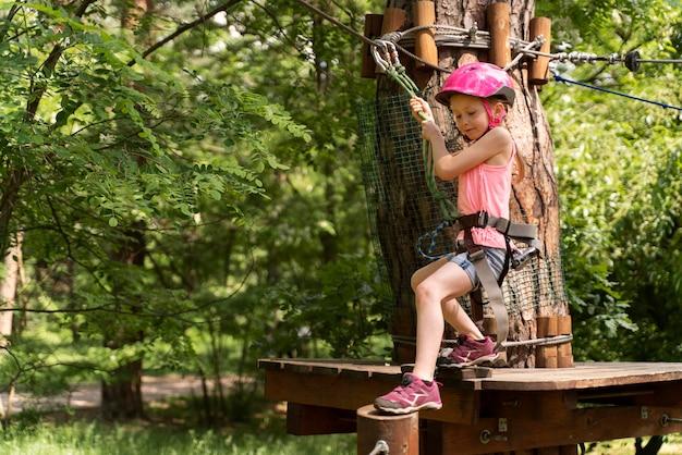 Chica guapa divirtiéndose en un parque de aventuras