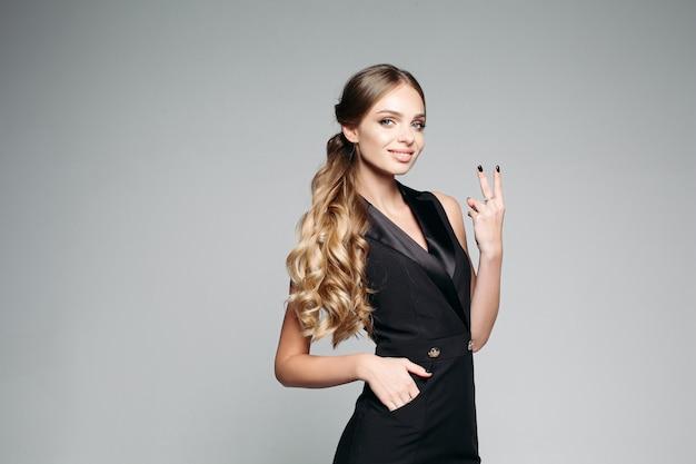 Chica guapa emocional en vestido negro, mostrando el signo de la paz y sonriendo a la cámara.
