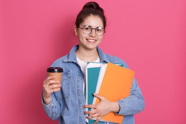 Chica guapa estudiante posando aislada sobre fondo rosado, dama vistiendo chaqueta vaquera y gafas