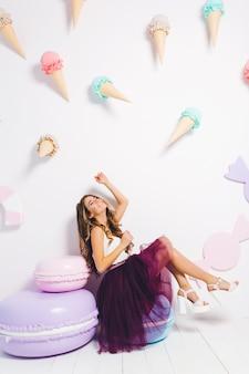 Chica guapa feliz en traje elegante relajante cerca de los grandes macarrones de colores, sentada con los ojos cerrados. retrato interior de una mujer joven increíble con rizos brillantes escalofriante