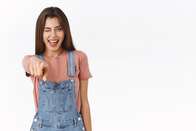 Chica guapa joven alegre en elegante outfing extender la mano y señalar con el dedo a la cámara, recogiéndote, tomando una decisión segura con una sonrisa complacida, guiñando un ojo descarado, de pie fondo blanco