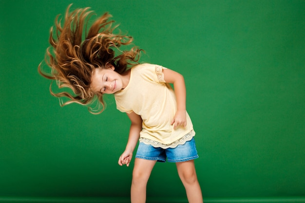 Chica guapa joven bailando sobre la pared verde