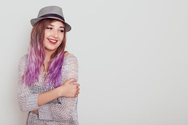 Chica guapa joven con cabello violeta, expresando amor, abrazándose a sí misma, mirando a otro lado con expresión soñadora, espacio de copia para publicidad, aislado sobre fondo gris.