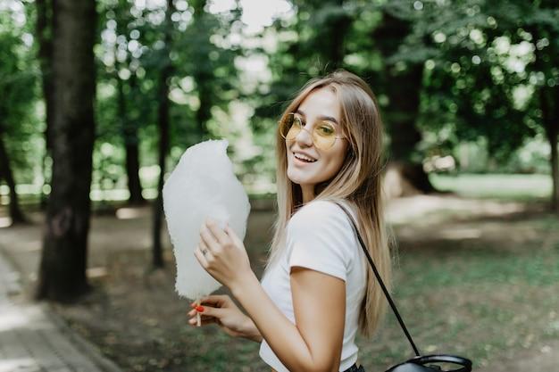 Chica guapa joven comiendo algodón de azúcar en el parque