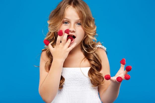 Chica guapa joven comiendo frambuesa sobre pared azul
