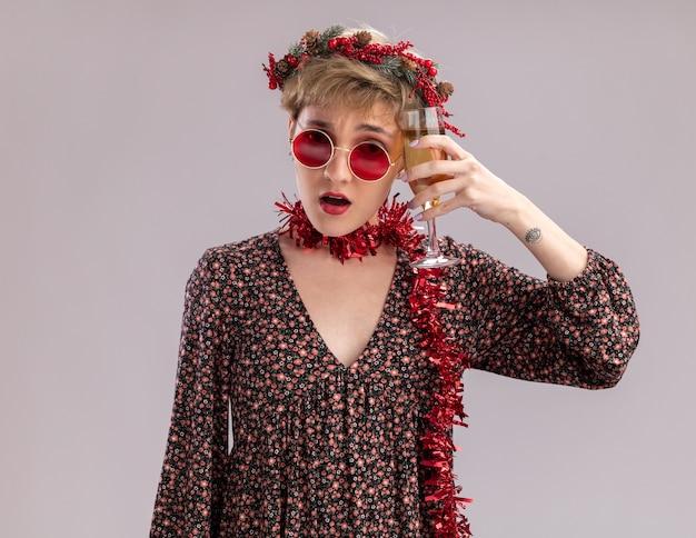 Chica guapa joven confundida con corona de navidad y guirnalda de oropel alrededor del cuello con gafas tocando la cabeza con copa de champán mirando a cámara aislada sobre fondo blanco