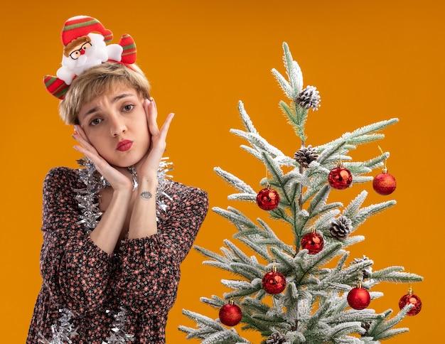 Chica guapa joven confundida con diadema de santa claus y guirnalda de oropel alrededor del cuello de pie cerca del árbol de navidad decorado mirando a la cámara manteniendo las manos en la cara aislada sobre fondo naranja