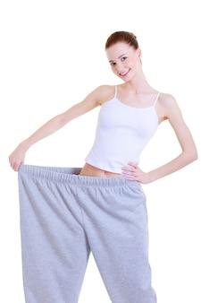 Chica guapa joven delgada en los pantalones grandes después de la dieta
