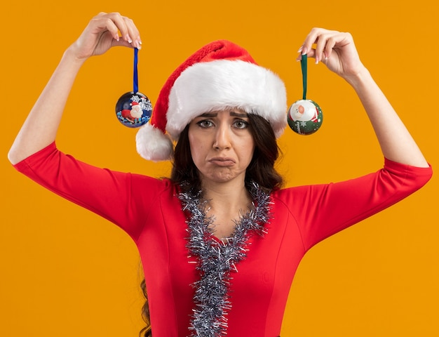 Chica guapa joven despistada con gorro de papá noel y guirnalda de oropel alrededor del cuello levantando adornos navideños aislados en la pared naranja