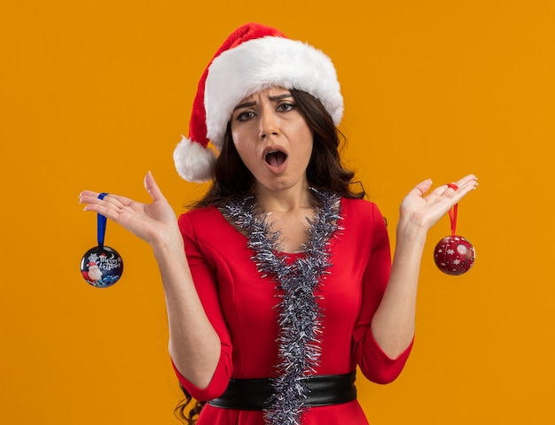 Chica guapa joven despistada con gorro de papá noel y guirnalda de oropel alrededor del cuello sosteniendo adornos navideños aislados en la pared naranja
