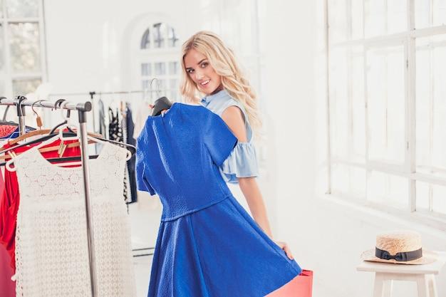 Chica guapa joven eligiendo y probándose vestidos en la tienda