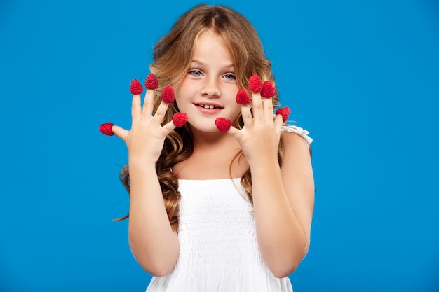 Chica guapa joven con frambuesa sobre pared azul